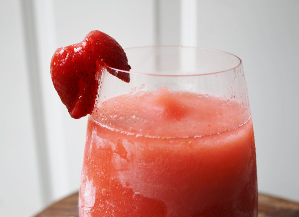 boozy strawberry lemonade slushie | frozen strawberries, pink lemonade, and a good slosh of tequila. The perfect summer cocktail! Get the recipe at: www.whatkumquat.com